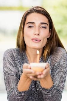 Retrato de mujer hermosa celebración cupcake de cumpleaños con una vela