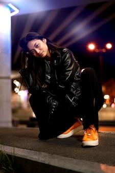 Retrato de mujer hermosa en la ciudad por la noche