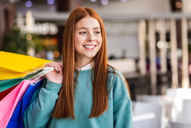 Retrato de mujer hermosa con coloridas bolsas de papel