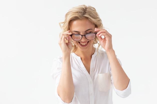 Retrato de mujer hermosa concentrada con mala visión tocando gafas aisladas en blanco