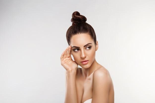 Retrato de mujer hermosa, concepto de cuidado de la piel, cuidado de la piel. dermatología. retrato de manos femeninas con uñas de manicura tocando su rostro.