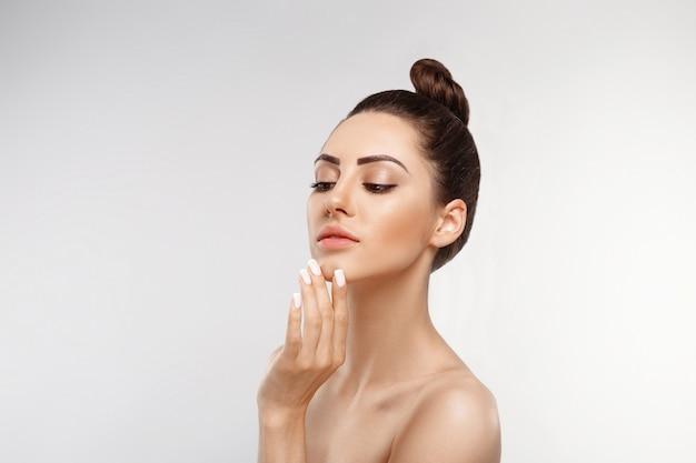 Retrato de mujer hermosa, concepto de cuidado de la piel, piel hermosa. retrato de manos femeninas con uñas de manicura.
