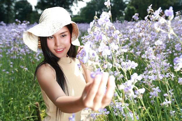 Retrato de mujer hermosa divirtiéndose y disfrutando entre flores naga-crested field en la naturaleza