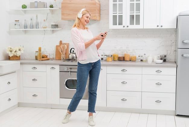 Retrato de mujer hermosa escuchando música en la cocina