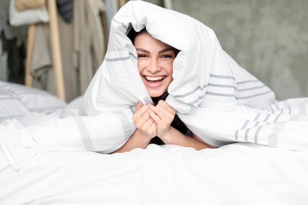 Retrato de mujer hermosa feliz en la cama