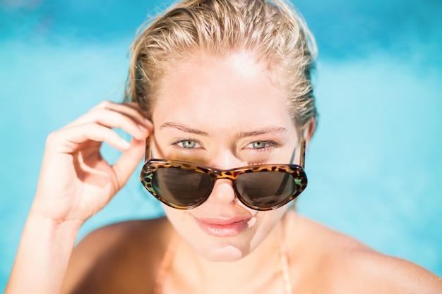 Retrato de mujer hermosa con gafas de sol inclinada junto a la piscina