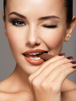 Retrato de mujer hermosa glamour sostiene y come dulces de chocolate.