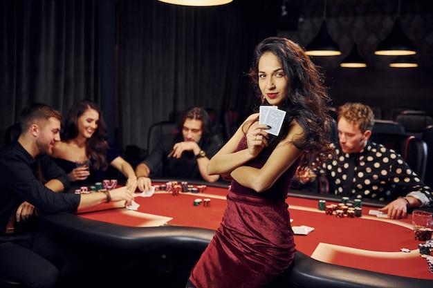 Retrato de mujer hermosa grupo de jóvenes elegantes que juegan al póker en el casino juntos