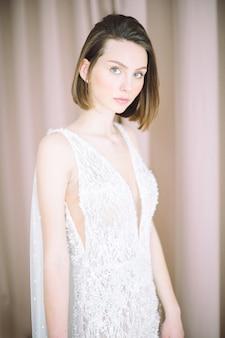 Retrato de mujer hermosa en la habitación de pie y mirando con vestido blanco largo