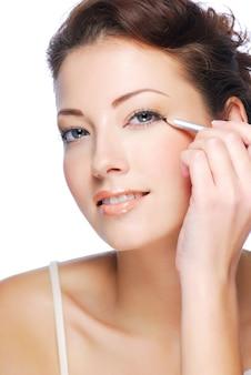 Retrato de mujer hermosa haciendo maquillaje con lápiz cosmético negro