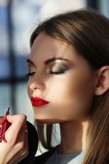 Retrato de mujer hermosa haciendo maquillaje