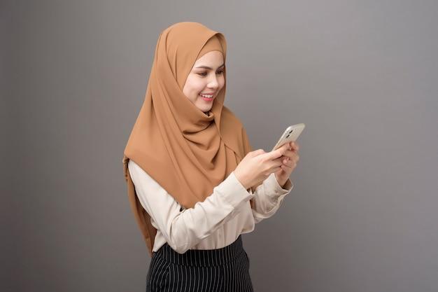 Retrato de mujer hermosa con hijab usando un teléfono celular en la pared gris