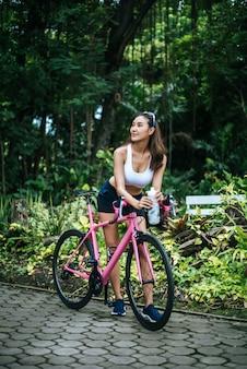 Retrato de la mujer hermosa joven con la bici rosada en el parque. mujer sana y atractiva.
