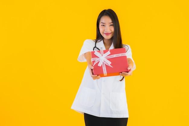 Retrato de mujer hermosa joven médico asiático mostrando caja de regalo roja