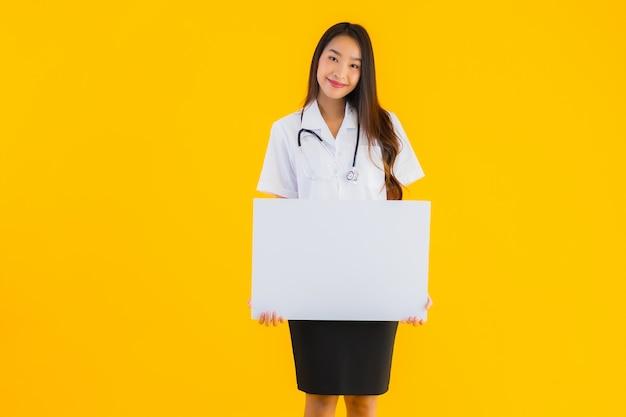 Retrato de mujer hermosa joven médico asiático con pizarra vacía