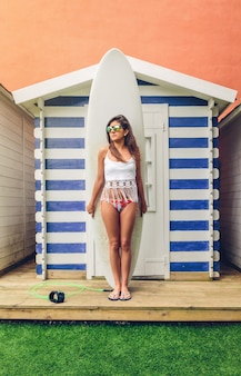 Retrato de mujer hermosa joven surfista con top blanco y bikini destacándose frente a su tabla de surf. concepto de ocio de verano.