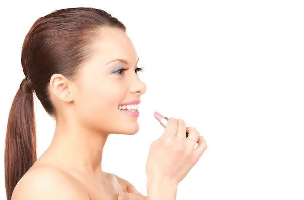 Retrato de mujer hermosa con lápiz labial sobre pared blanca