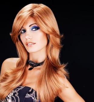 Retrato de una mujer hermosa con largos pelos rojos y maquillaje de ojos azul de moda - en la pared negra