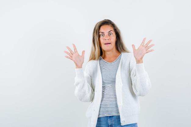 Retrato de mujer hermosa levantando las manos en gesto de rendición en chaqueta, camiseta y mirando asustado vista frontal