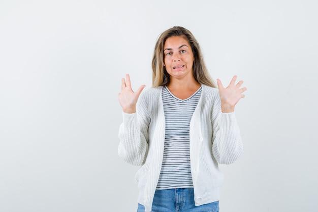 Retrato de mujer hermosa levantando las manos en gesto de rendición en chaqueta, camiseta y mirando confusa vista frontal