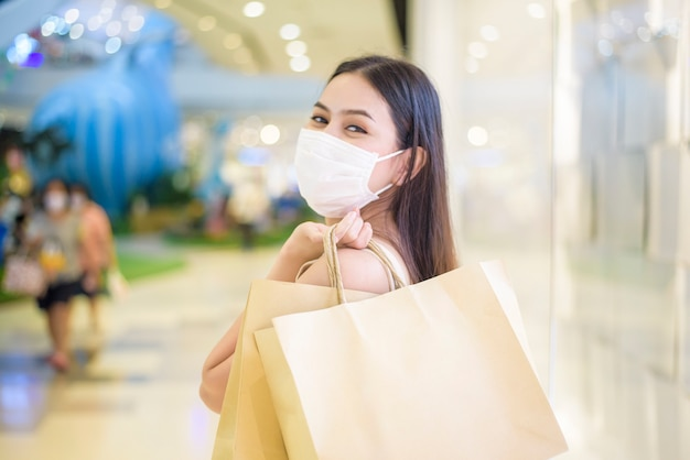 Retrato de mujer hermosa lleva mascarilla en el centro comercial