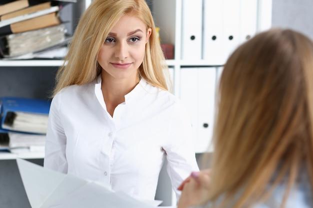 Retrato de mujer hermosa en el lugar de trabajo examinando estadísticas financieras.