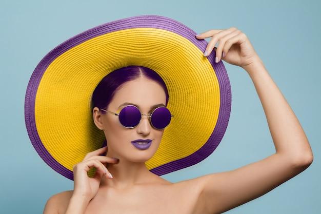 Retrato de mujer hermosa con maquillaje brillante, sombrero y gafas de sol en estudio azul