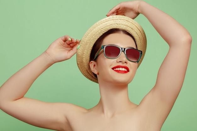 Retrato de mujer hermosa con maquillaje brillante, sombrero y gafas de sol sobre fondo verde de estudio. hacer y peinado elegante y de moda. colores de verano. concepto de belleza, moda y publicidad. sonriente.