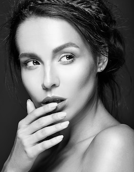 Retrato de mujer hermosa con maquillaje diario fresco tocando su boca