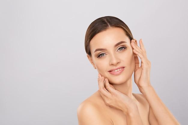 Retrato de mujer hermosa con maquillaje natural tocando su rostro.
