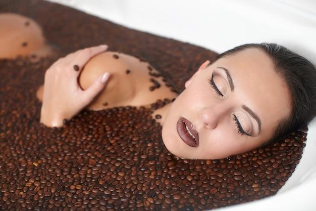 Retrato de mujer hermosa moda en jacuzzi con café. cuidado del cuerpo. maquillaje brillante