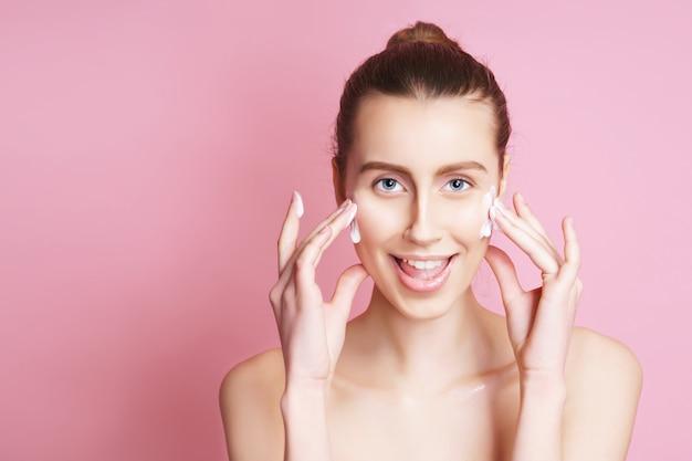 Retrato de mujer hermosa modelo con maquillaje natural, aplicar la crema en la cara. aislado en rosa