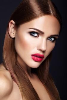 Retrato de mujer hermosa modelo con maquillaje de noche y peinado romántico. labios rojos