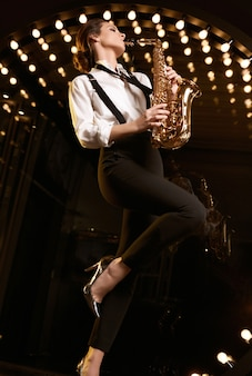 Retrato de mujer hermosa modelo morena en traje formal de moda con saxofón tocando en restaurante