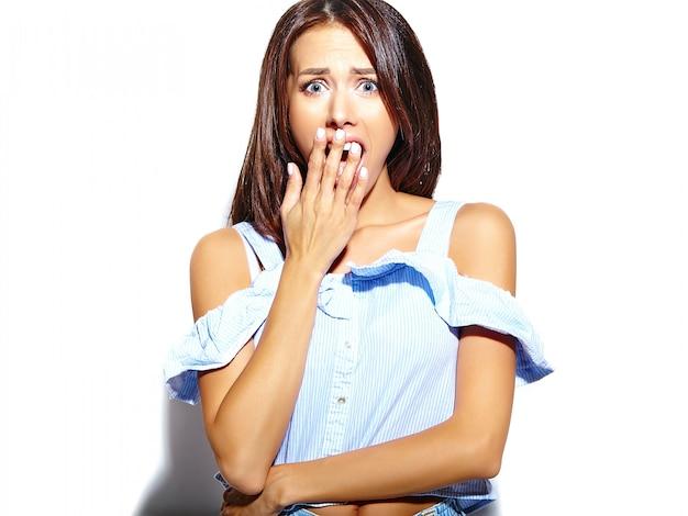 Retrato de mujer hermosa mujer sorprendida cubre su boca abierta con la mano, aislado en blanco