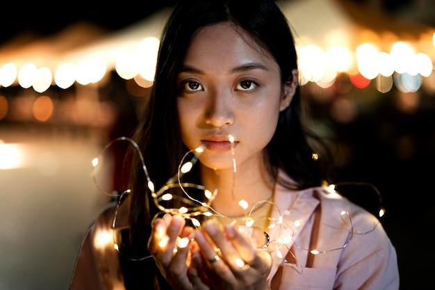Retrato de mujer hermosa por la noche en las luces de la ciudad