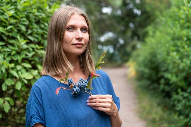 Retrato de mujer hermosa con ojos azules en vestido azul está de pie en un camino en el parque contra backg ...