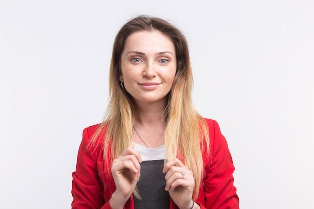 Retrato de mujer hermosa pecosa sonriente con la mano en la barbilla, vestida de rojo
