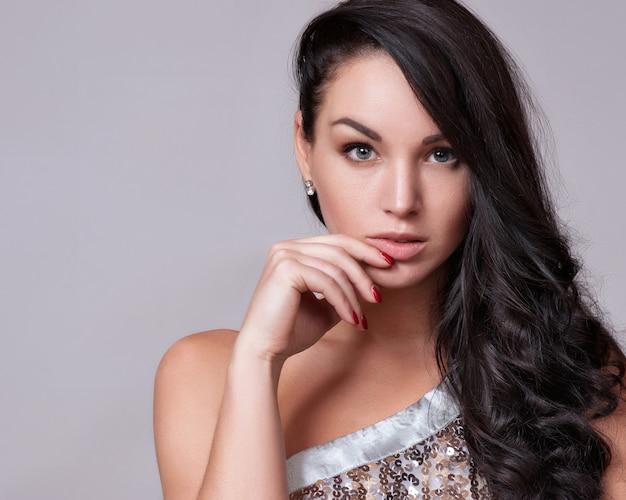 Retrato de mujer hermosa con peinado rizado y maquillaje brillante
