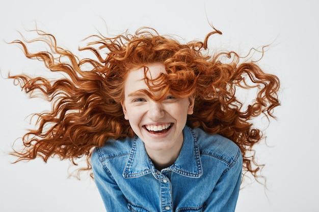 Retrato de mujer hermosa pelirroja alegre con pelo rizado volando sonriendo riendo.
