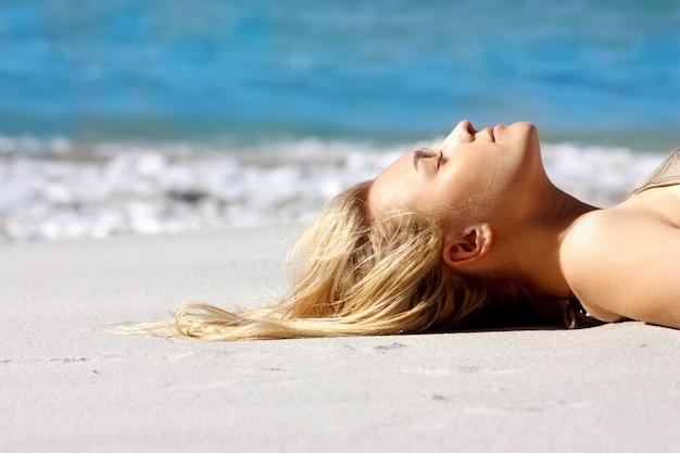 Retrato de mujer hermosa con el pelo largo y rubio en la playa