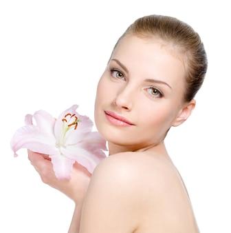 Retrato de mujer hermosa con piel sana sosteniendo una flor cerca de la cara - aislada