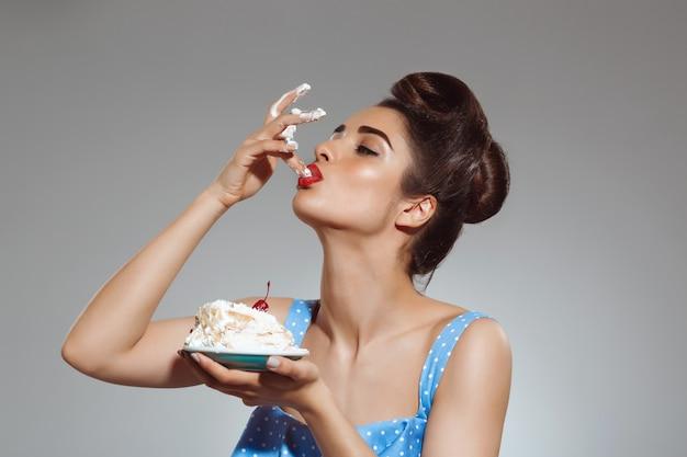 Retrato de mujer hermosa pin-up comiendo pastel