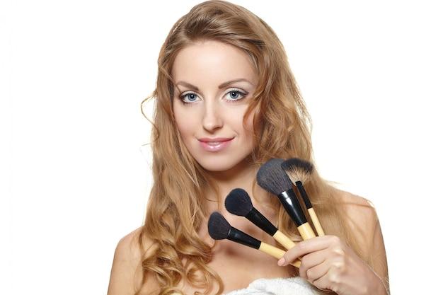 Retrato de mujer hermosa con pinceles de maquillaje