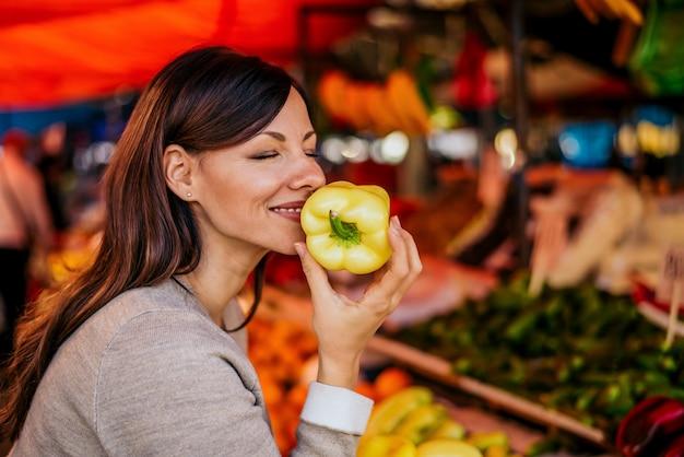 Retrato de la mujer hermosa que huele paprika en el mercado. el olor de las verduras frescas es increíble