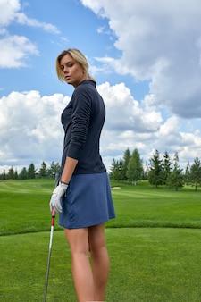 Retrato de una mujer hermosa que juega a golf en un fondo verde del campo al aire libre. el concepto de golf, la búsqueda de la excelencia, la excelencia personal, el deporte real.