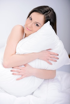 Retrato de la mujer hermosa que se relaja en la cama.