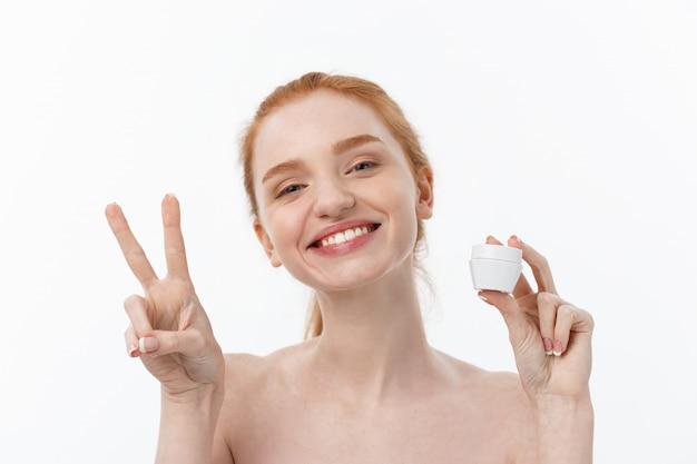 Retrato de la mujer hermosa que sonríe mientras que toma un poco de crema facial aislada en el fondo blanco con el espacio de la copia.