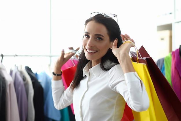 Retrato de la mujer hermosa que sostiene los paquetes coloridos con las compras en manos detrás detrás. mujer maravillosa haciendo compras en el famoso showroom. concepto de compras y moda