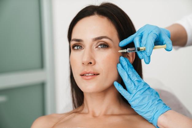 Retrato de mujer hermosa recibiendo tratamiento de mesoterapia en la cara por especialista en guantes en salón de belleza